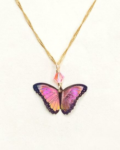 Pink and orange gradient butterfly with black outline on a gold chain with a peach colored bead.