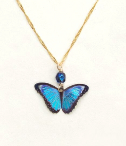 A bright blue realistic butterfly pendant with black outlines on a gold chain and a shiny dark blue bead.