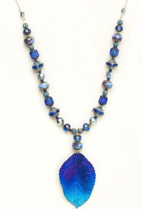 Navy to light blue elm leaf necklace on a silver chain with beads going about halfway up in shades of blue.