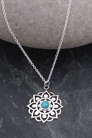 sterling silver floral mandala pendant with small circular turquoise stone in center.