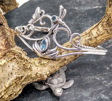 Load image into Gallery viewer, Silver cuff with a lotus sitting at the bottom with a diamon shaped blue topaz as its center. Three curls on the left and two of the right meet upwards above the lotus. There is a butterfly between the top two curls on the left and a dragonfly with circular blue topaz for a head is at the top center.