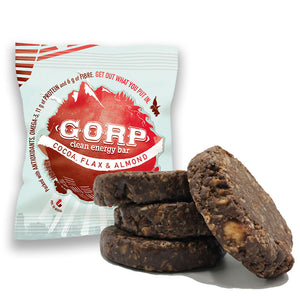 Cocoa Flax & Almond GORP Clean Energy Bar with bar package and three bars piled up with one resting to the right of the pile, showing ingredients of bar.