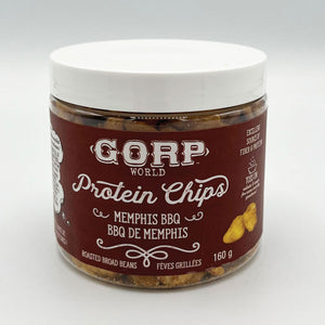 Memphis BBQ Protein Chips by GORP World.  Image shows a 150g jar with Memphis BBQ flavored roasted broad beans.  Clear jar.  White label with black font.  Black lid.  A small pile of Memphis BBQ chips lays to the right of the jar on a wood charcuterie board.