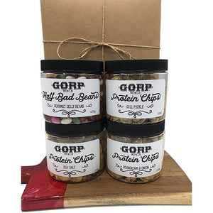 Sweet & Salty Gift Box.  1 jar of Half Bad Beans - Gourmet Jelly Beans and 3 jars of Protein Chips, any flavor assortment.  Image shows 4 jars, with 2 stacked on top of each other on a wood chartcuterie board and a kraft brown gift box tied up with string behind the jars