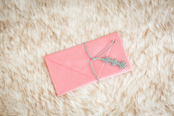 This is a peach Korean inspired money envelope and was crafted by Koreans in Korea. The design of the knot shows that this was handcrafted.