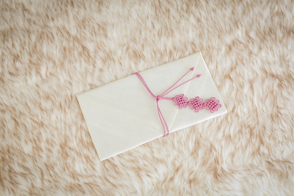 This Korean money wallet is in white pink. White is a common color for money wallets used for specific Korean celebrations.