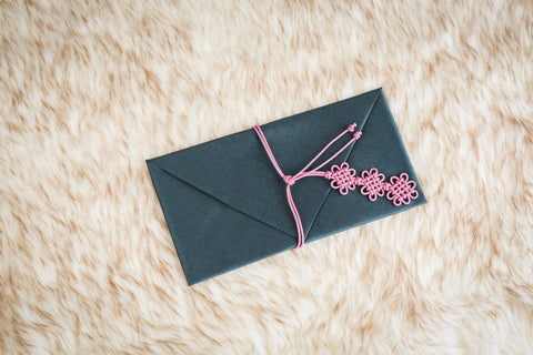 This is a teal colored daisy Korean money envelope made in Korea. The string around the wallet is a norigae that is floral inspired for a beautiful look.