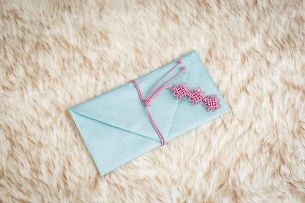 This is a mint colored daisy Korean money envelope. This color was one of the colors used by the female side of the family to send the male's side of the family with money, a letter, or another form of value as a sign of respect an a bright future with each other.