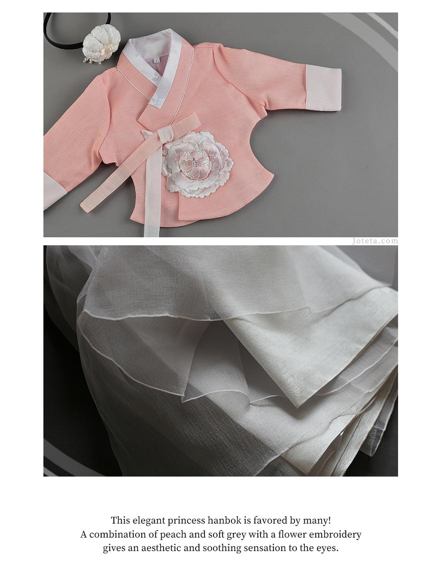 The salmon and silver baby girl hanbok looks timeless and traditional and baby girl will be smiling non-stop wearing it.