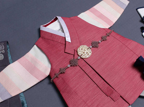 This picture is an up close image of the top of the baby boy hanbok in brick red. It's designed to be comfortable and also traditional.