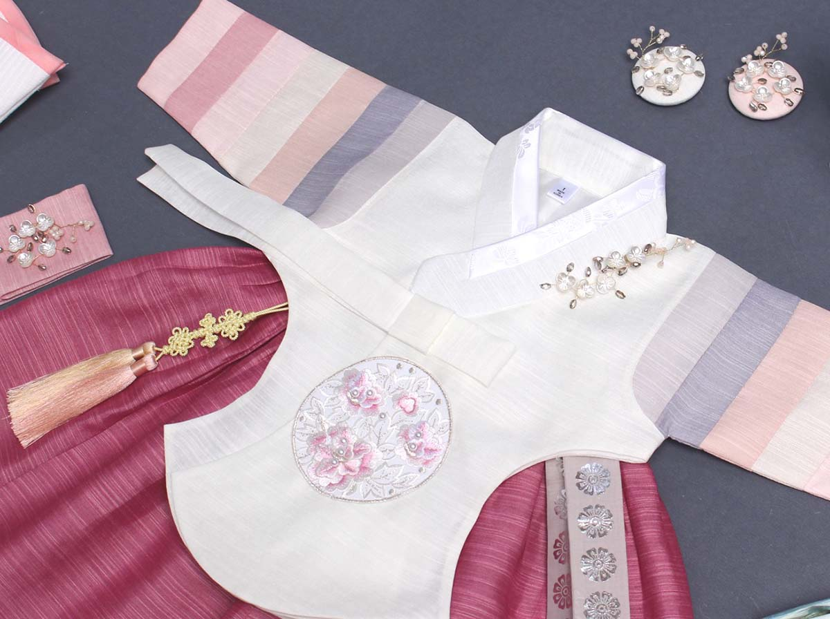 This picture shows the Saekdong Jeogori and how captivating it looks with the coral and off-white girl hanbok.