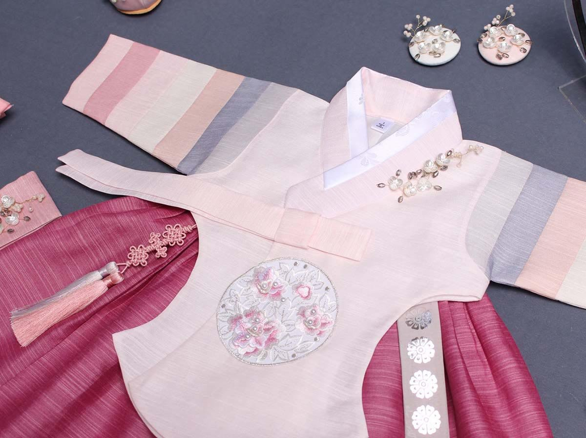 The Saekdong Jeogori adds a playful feel to the baby girl hanbok in dark pink and light pink.