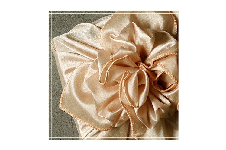 A closer look at the bow placed neatly at the top of the beige colored reusable gift wrap.