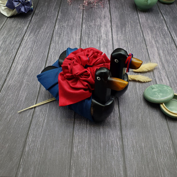 Black wooden Korean wedding geese that are color coded with a ribbon tied around it's beak.