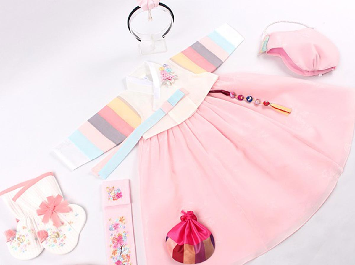 The Saekdong Jeogori is much more visually attention-getting and your baby girl will feel the love when she wears this creamy and salmon colored hanbok.