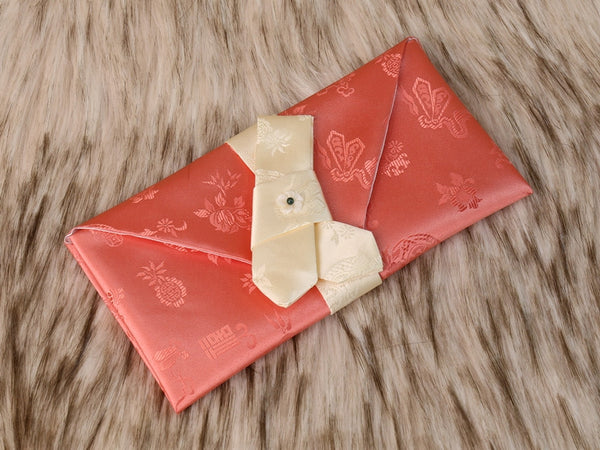 The Orange Cloud crane money envelope has a unique look with its shade of orange. The ribbon that's tied to secure the envelope is in beige and a beautiful floral pendant is attached.