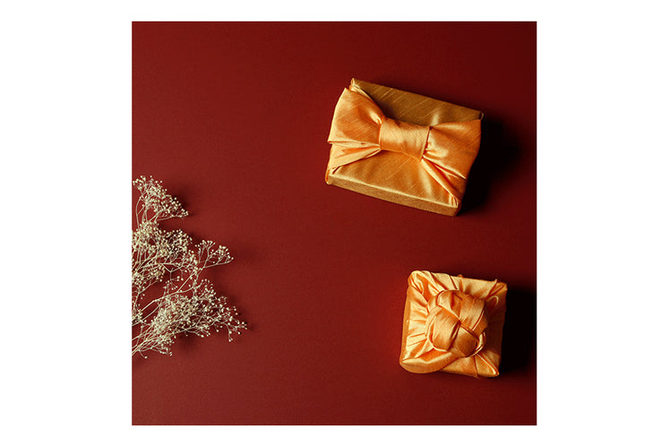 Adding an chic spiral at the top of the apricot Bojagi reusable gift wrap makes it look even more glamorous.