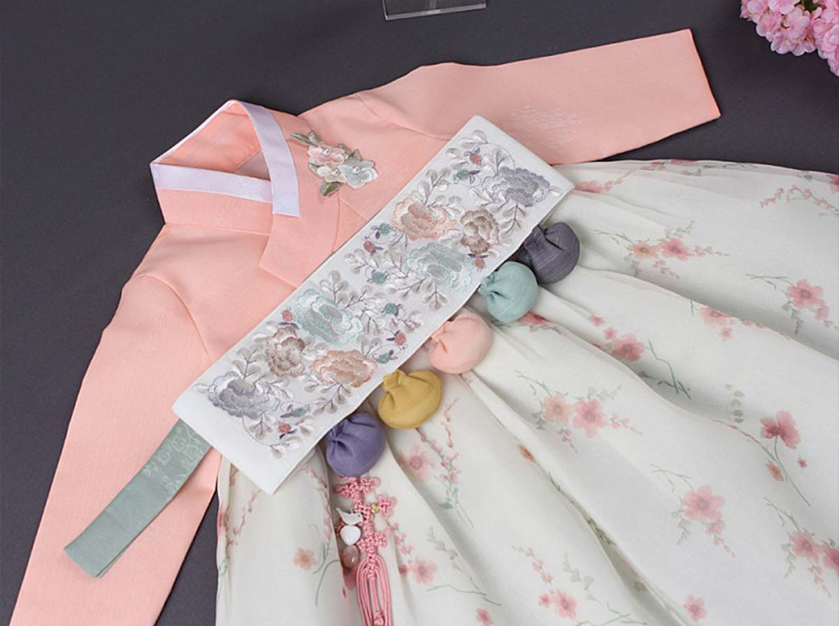 The Dol belt is part of the Dol baby girl hanbok in flower and pink. A baby girl will feel like a lovely spring flower when she puts on this hanbok.