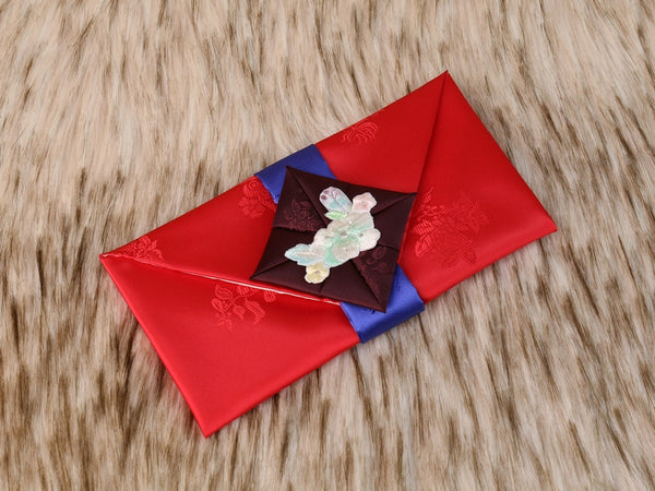 Furoshiki themed Korean money wallet in red. This has a handmade floral embroidery near the opening of the envelope and is beautiful when seen in person.