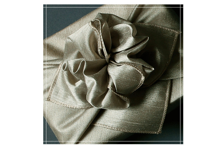 An intricate bow added to the top of the sage fabric wrapping paper turns this into Bojagi art.