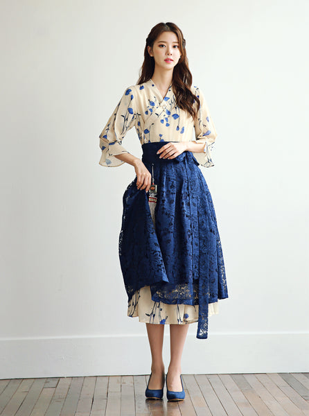 A modern hanbok dress in indigo and fawn still retains the traditional elements of the Korean hanbok, but is designed to be worn anytime for any special occasion.