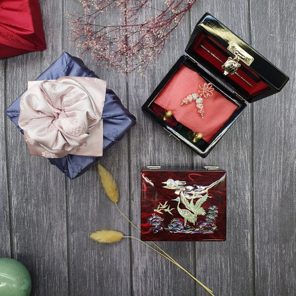 The inside of the Songhak Mother of pearl wedding gift set. Inside sits a wedding duck that's covered with a fortune pouch.