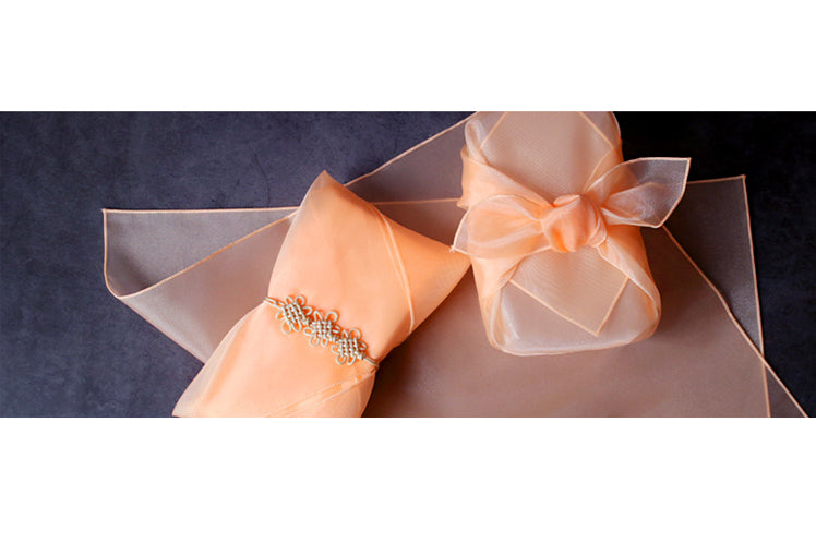 You can add charms and tassels to the burnt orange lucid Korean Bojagi to add a personal touch to the gift wrapping cloth.