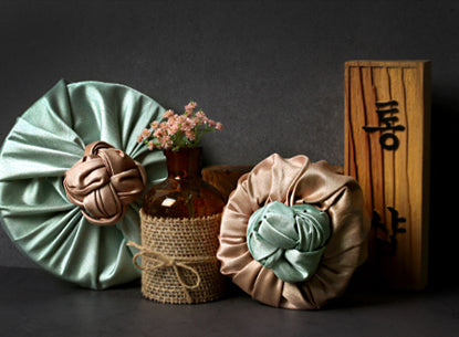 You can use the bronze and olive Korean Bojagi Art to dress up decorations around your home so it's more than just a wrapping cloth.