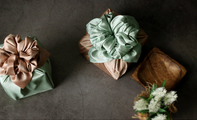 A beautiful bow at the top of this sage and khaki Bojagi wrapping is the perfect ending to wrapping presents with fabric.