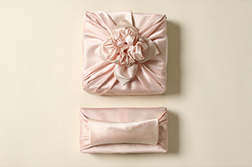 Light coral and flush are great choices for fabric wrapping cloth if you're attending a baby girl Doljanchi.