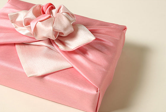 Wrapping presents with fabric, such as this hot pink and dull ivory Bojagi, bring opulence and radiance to any Korean holiday.