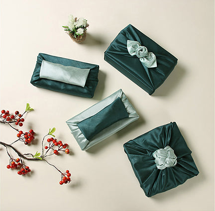 Wrapping presents with fabric, such as this Oxford blue and sap, is bringing a personal touch to any gathering.