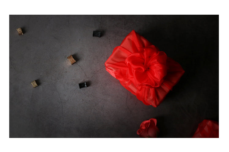 Convoluted bows add to the grace of this brick red reusable gift wrap.