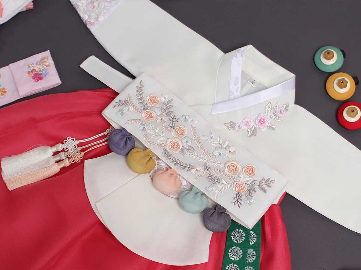 A Dol belt comes with the Dol version of the baby girl cherry red and light ivory hanbok.