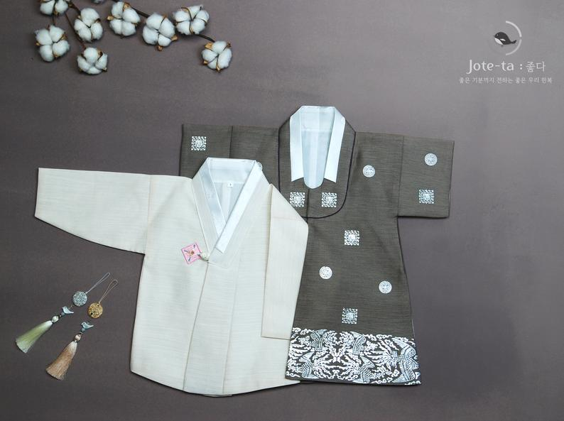 The royal baby boy hanbok in brown is unique in the sense that it is full of Korean characters and images that represent Korean culture.