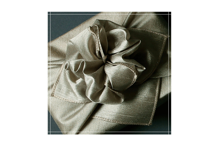Learn how to impress your friends with the bow on the gray single sided Bojagi gift wrapping paper.