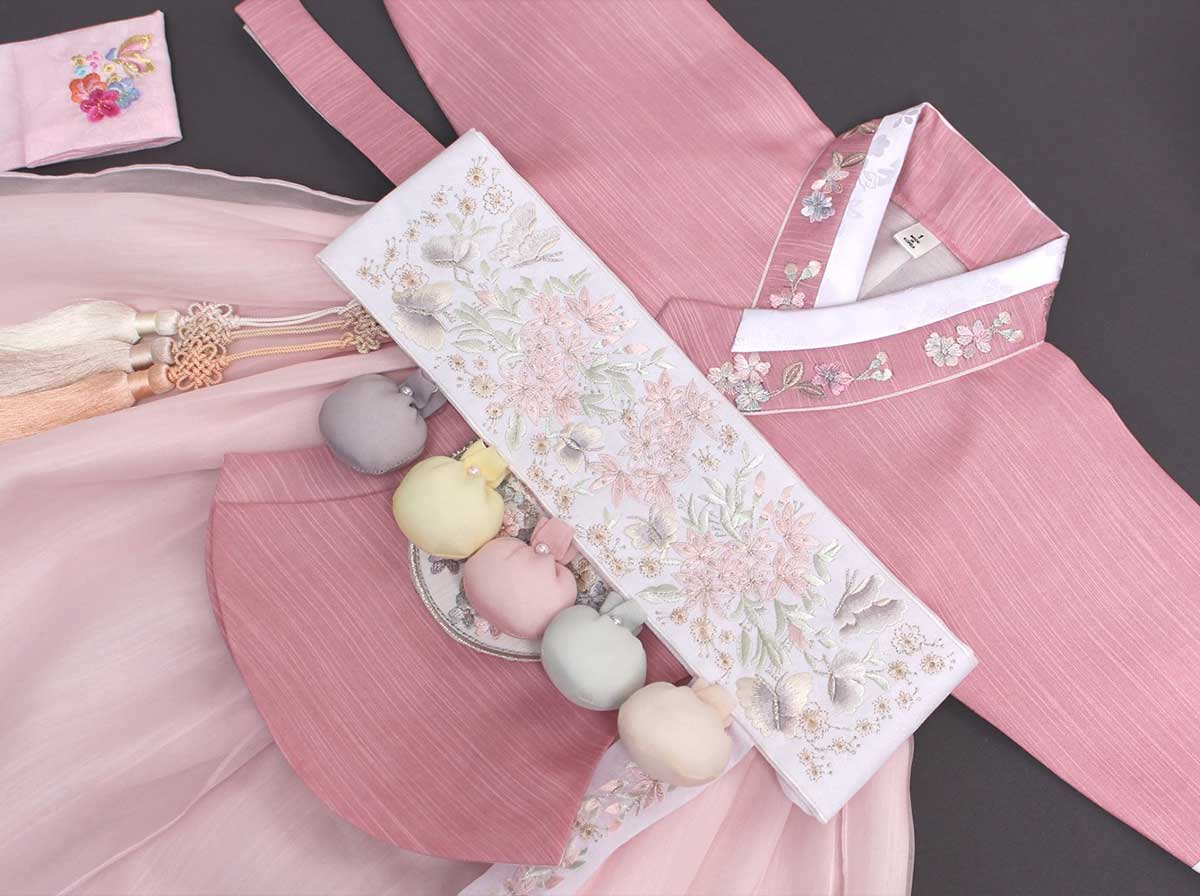 An up close look at the intricate details and decorations on the Yuma baby girl hanbok in rouge.
