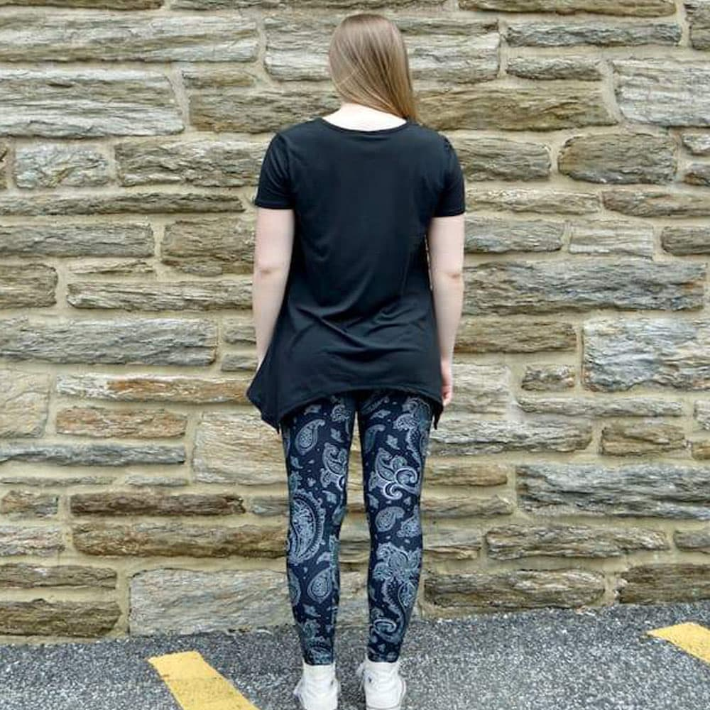 Model showing back view of black paisley pattern leggings by Jolina Boutique