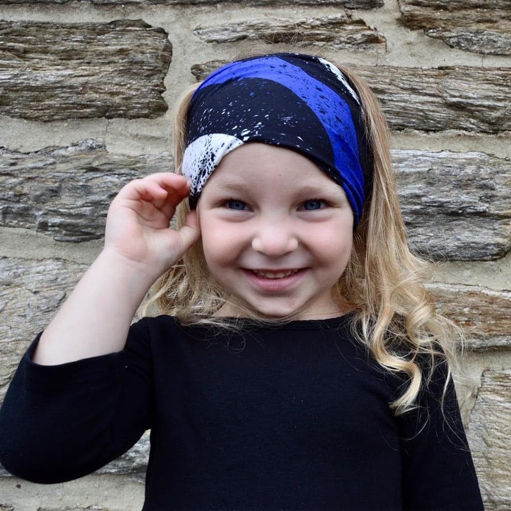 Little girl wearing a blue line pattern face cover as a headband by Jolina Boutique