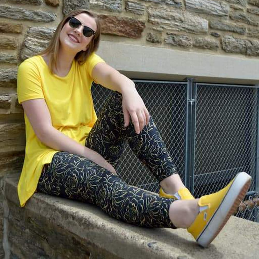 Model sitting on ledge wearing golden rose pattern leggings by Jolina Boutique