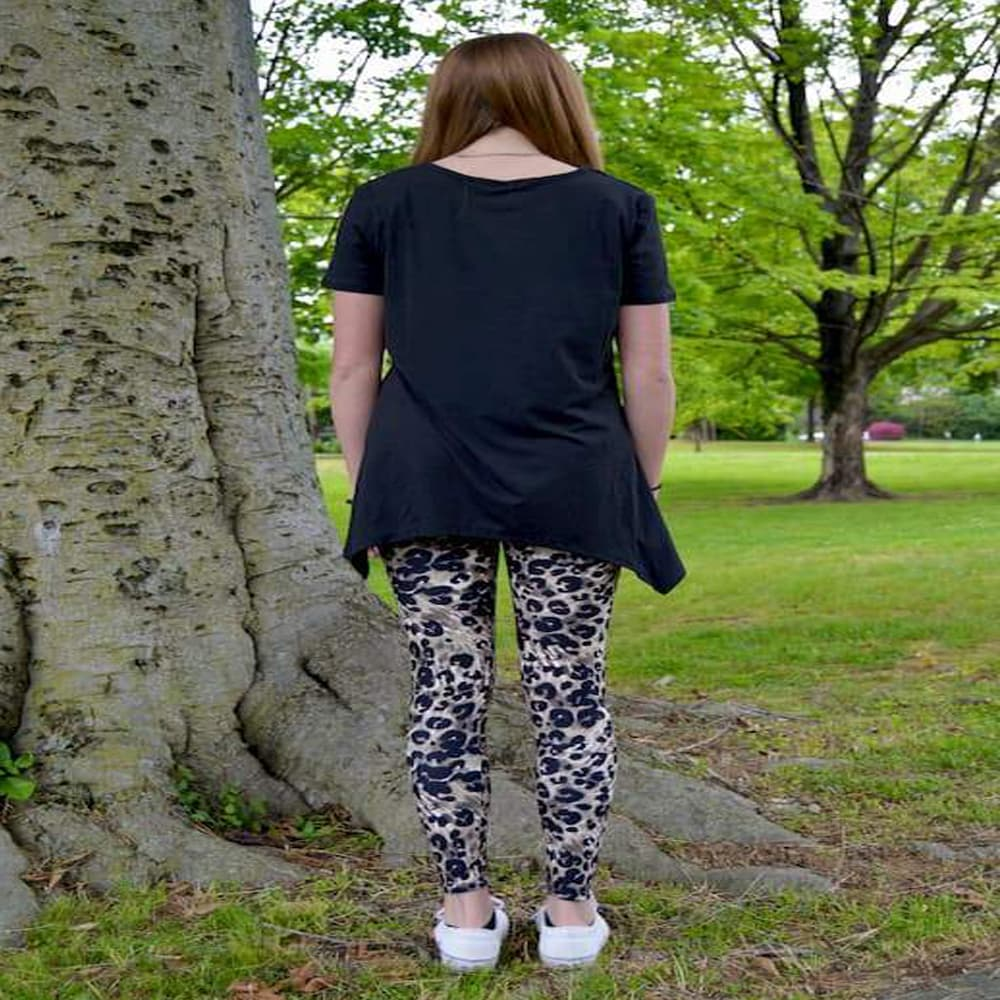 Model showing back view of her leopard pattern leggings sold by Jolina Boutique