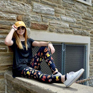 Model posing on ledge wearing philadelphia themed pattern leggings sold by Jolina Boutique