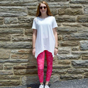Model standing in front of wall wearing pink camo leggings