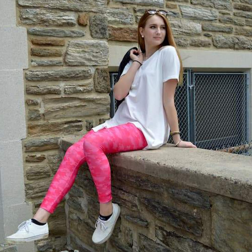 Model sitting on ledge wearing pink camo leggings