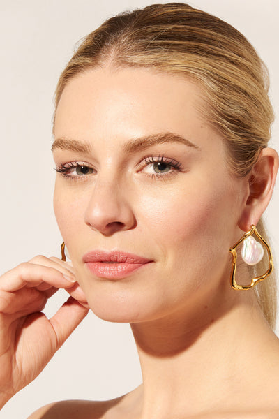 Thumbnail of model wearing the Formation Earrings In Pearl. These gold-plated abstract statement earrings are artistic, earthy and elegant-- talk about a fantastic union! With hanging freshwater pearl drops for a luminous look.