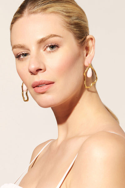 Thumbnail of model wearing the Formation Earrings In Pink. These gold-plated abstract statem...