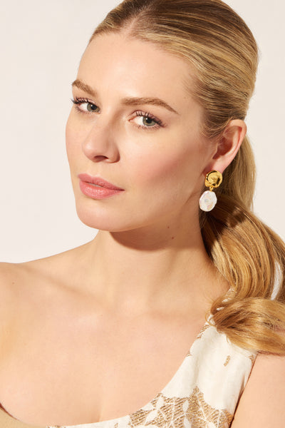 "Thumbnail of model wearing the Coin Reflection Earrings. Our understated gold ""coin"" top ear..."