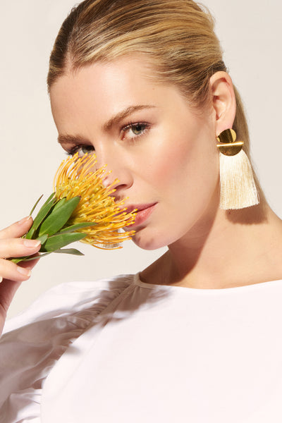 Thumbnail of model wearing the Crater Earrings In Cream. Our beloved Crater Earrings are the perfect marriage of chic polish and edgy fun. With sculptural gold-plated discs and elegant cream silk tassels.