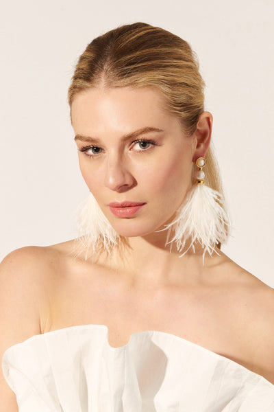 Thumbnail of model wearing the Parker Earrings In Ivory. There's no other way to say it-- these frothy ivory feather earrings are outfit game-changers and all-out statement-makers. A bouquet of ostrich feathers are capped with gold-plated beads, baroque pearls and mother-of-pearl tops.