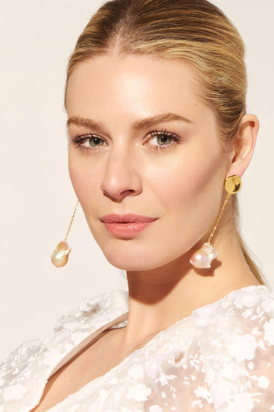 Thumbnail of model wearing the Lotus Drop Earrings. Dance the night away in these swingy stunners; these gold-plated chain earrings with hanging baroque pearls channel ease and elegance.